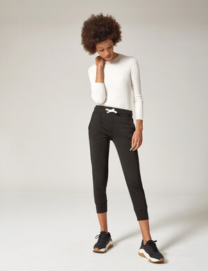 Product Pantalon de jogging femme, noir, 2 poches devant, 1 poche dos avec patch, finitions bords côtes, taille élastiquée avec lien de resserrage. Photos retouchéesMarque Jennyfer Catégorie joggness