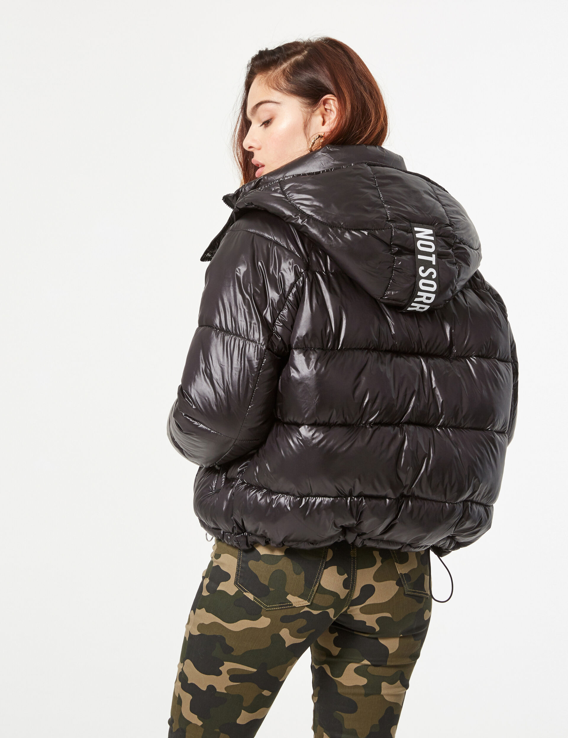 Padded jacket with 'not sorry' slogan