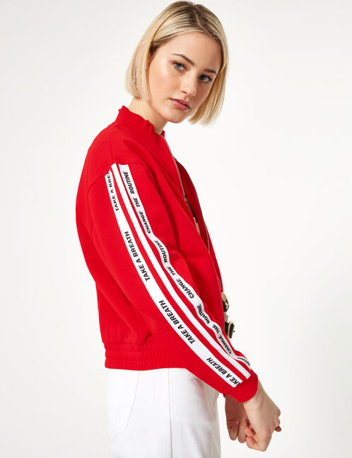 Red and white zip-up sweatshirt with text design detail